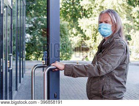 Elderly Man In Protective Mask Opens The Door To The Store Outdoor On Autumn Day