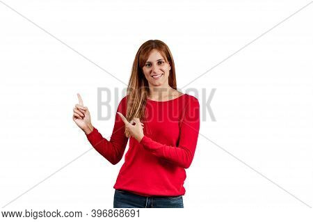 Beautiful Young Woman In A Red Sweater, Pointing Her Hands At The Copyspace, Isolated On A White Bac