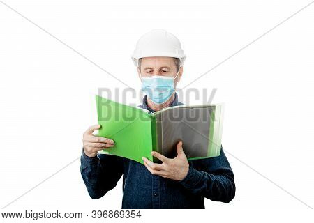 Middle Aged Contractor Or Architect Holding A Notepad, Wearing Protective Helmet And Face Mask Prote