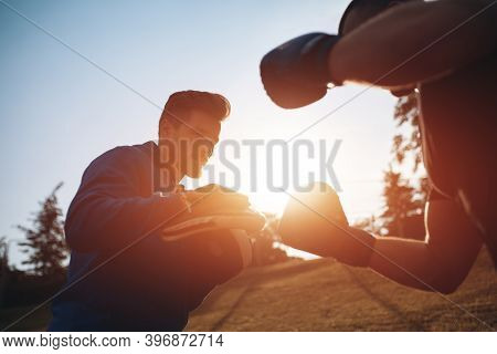 Sport Man Boxer Exercising In Boxing Gloves With Personal Trainer Outdoor