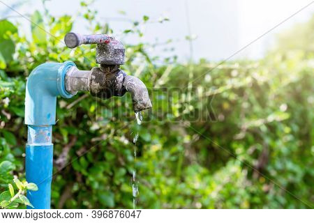 Close-up Of An Old Water Tap Or Faucet Leaking Drop Of Water With Green Nature Background- Water Con