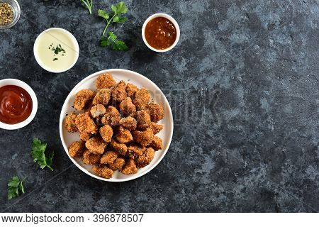 Crispy Fried Breaded Chicken Bites In White Bowl Over Blue Stone Background With Copy Space. Tasty C