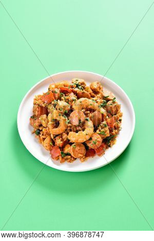 Creole Jambalaya With Chicken, Smoked Sausages, Rice And Vegetables On Plate Over Green Background W