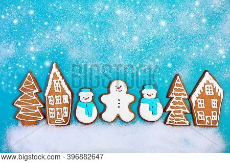 Christmas Ginger Snowmen And Gingerbread Houses And Fir Trees On A Snowy Blue Background. Concept Of