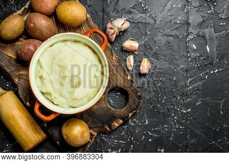 Mashed Potatoes In A Bowl With Garlic . On Black Rustic Background.