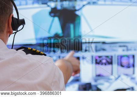 Captain of commercial airplane changes the autopilot settings in the cockpit of a flying airplane
