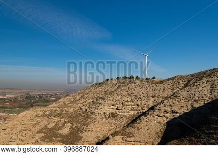 Isolated Wind Turbine On Top Of A Hill With Semi-desert Landscape And A Valley In The Background