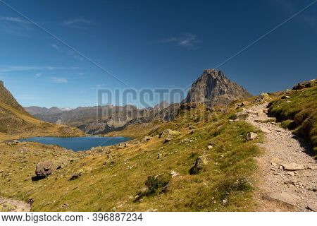Mountain Path With A Lake And The Midi D'ossau Peak In The Background Surrounded By Mountains And Na