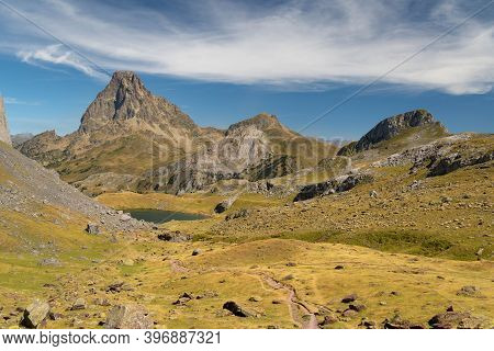 Mountain Path With A Lake And The Midi D'ossau Peak In The Background Surrounded By Mountains, Rocks