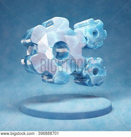Cog Wheels Icon. Cracked Blue Ice Cog Wheels Symbol On Blue Snow Podium. Social Media Icon For Websi