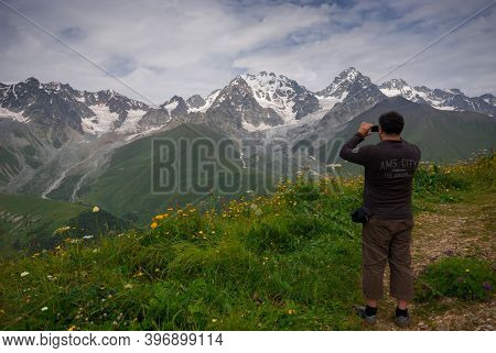 Georgia, Racha - August 16, 2013: The Traveling Man Enjoys A Magnificent View Of The Mountains.