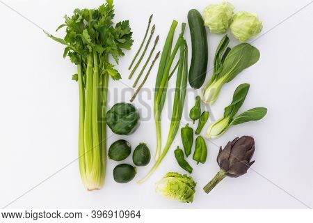 Celery, cucumber, lettuce and peppers on white background. fresh produce green vegetables healthy eating organic food preparation concept.
