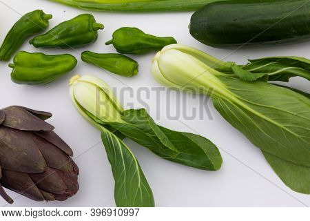 Cucumber, peppers and chicory on white background. fresh produce green vegetables healthy eating organic food preparation concept.