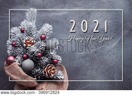 Happy New Year 2021 Text. Small Christmas Tree In Sackcloth Decorated With Red Baubles And Berries