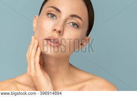Studio Portrait Of Young Woman With Natural Makeup, Combed Hair, Touching Well-groomed Pure Skin On