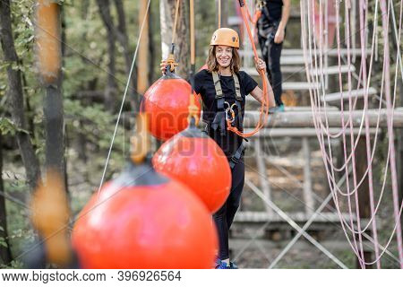 Well-equipped Man And Woman Having An Active Recreation, Climbing Ropes In The Park With Obstacles O