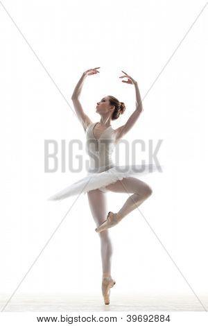 silhouette of ballerina in classical tutu in the white studio