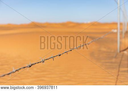 Single Barbed Wire With Desert Dunes In The Background In Al Madam Ghost Village, United Arab Emirat