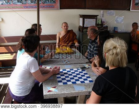 Chiang Mai, Thailand, April 25, 2016: Group Of Tourists Chat With A Buddhist Monk Next To The Wat Ch