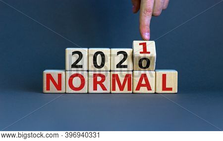 Time To 2021 Normal. Male Hand Turns A Cube And Changes Words '2020 Normal' To '2021 Normal'. Covid-