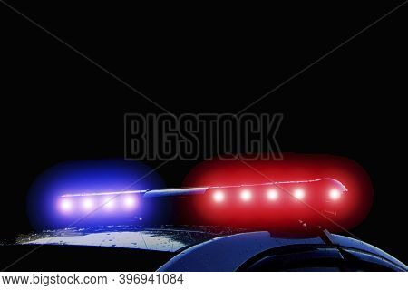 Police Car With Red And Blue Flashing Lights On Street At Night Time, Crime Scene. Emergency Vehicle