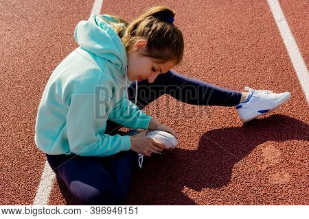 Sports Injuries, A Young Female Athlete Kneading An Ankle, Sprained Ligaments Or Muscles. Runner In
