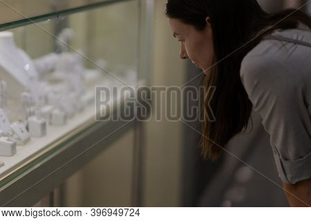 A Young Woman In A Store Admires A Display Of Jewelry With Diamonds And Precious Stones. Jewelry Sto