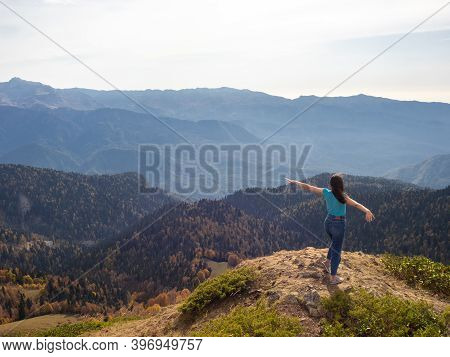 Tourist Stands On Top Of A Mountain With Her Arms Outstretched, Hiking In The Mountains. Enjoy The F
