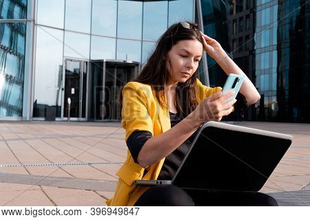 Freelancer With A Laptop Is Sitting On The Stairs Near The Business Center, A Young Woman In A Yello