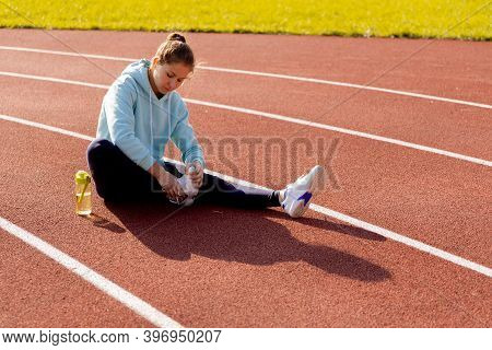 Outdoor Fitness, Public Sports Field. A Young Sportswoman Does A Workout On The Street, A Healthy Li