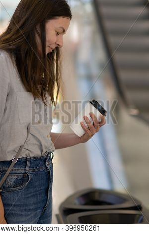 Sorting Garbage In Public Places. A Young Woman Chooses Where To Throw A Disposable Cup Of Coffee. C
