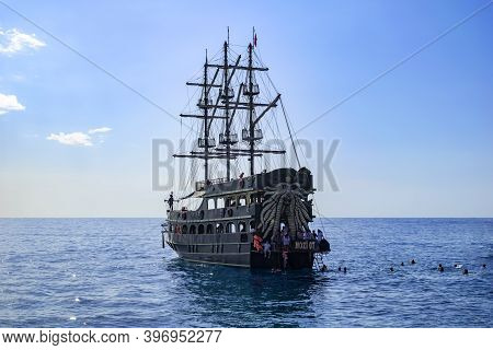 Turkey, Alanya - October 22, 2020: Vintage Pirate Ship And Tourists Swimming In The Water Near It In