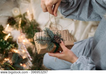 Woman Wrapping Christmas Gifts Near Xmas Tree At Home. Christmas Gift Boxes Wrapping Process. Female