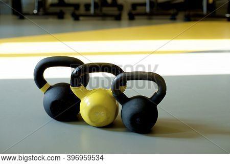 Three Kettlebells Stand In A Row On A Gray Floor In A Bright Fitness Room. Yellow Kettlebell, Black
