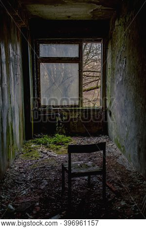 A Lonely Abandoned Chair Left Opposite The Window In The Ghost Town Of Pripyat, Chernobyl In Ukraine