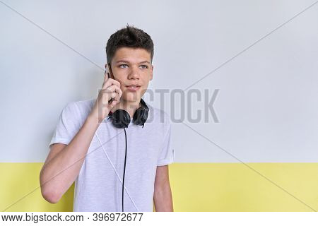 Portrait Of Student Teenager 16, 17 Years Old In White T-shirt With Headphones, Talking On Mobile Ph