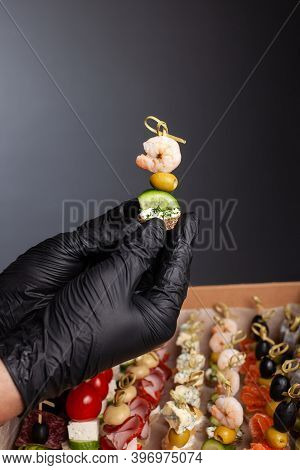 Canape, Hands In Black Gloves Hold A Beautiful Canape On A Cap. Catering, Snacking, Food. Studio Pho