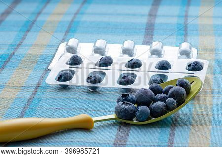 On The Blue Checkered Tablecloth Are A Yellow Spoon With Blueberries, A Blister Pack With Blueberrie