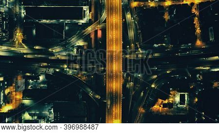 Top down night city traffic highway at lantern lights with illuminate cityscape aerial view. Downtown outdoor landscape with modern architecture of skyscrapers buildings. Cinematic urban Philippines