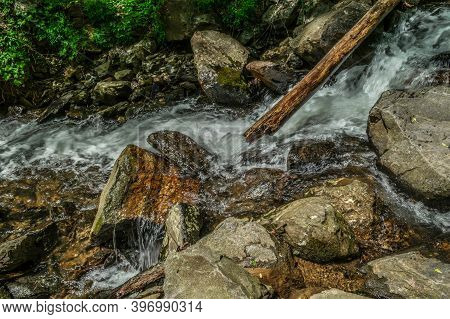 Fast Moving Whitewater Splashing Over The Rocks And Boulders Going Downstream From The Mountain With