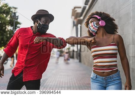 African Friends Wearing Face Protective Mask While Doing New Social Distance Greetings Bumping Elbow