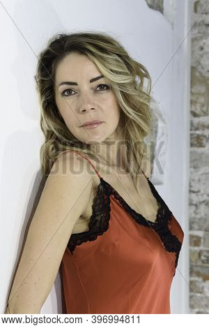 Close-up Of Blonde Girl In Red Petticoat In Silk Lingerie. Single Woman. White Background.