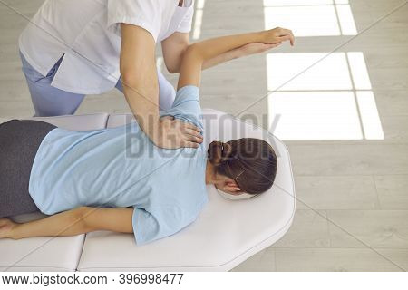 Hands Of Osteopath Masseur Doctor Fixing Lying Woman Patients Back And Shoulder