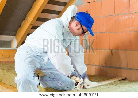 Worker in overall is cutting insulating material with gloves and knife