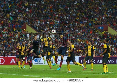 KUALA LUMPUR - AUGUST 10: Malaysia's Gurusamy (15) defends Barcelona's Sergio Busquets (maroon/blue) attack in a game at the Shah Alam Stadium on Aug 10, 2013 in Malaysia. FC Barcelona wins 3-1.