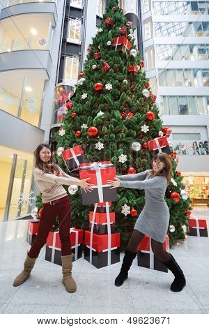 MOSCOW - DEC 20: Two employees of the bank with a gift in hands standing next to a large Christmas tree in the Main office Rosbank on December 20, 2012 in Moscow, Russia.