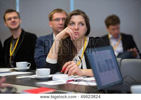 MOSCOW - DEC 20: The girl sits at a table and listen to the speaker on Business Breakfast at the office Rosbank on December 20, 2012 in Moscow Russia.
