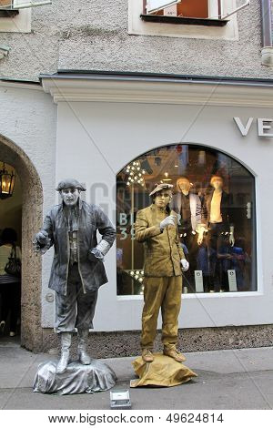 SALZBURG, AUSTRIA - AUGUST, 2012 : Street performers - Gold and Silver men pose on the shopping street (Getreidegasse, Grain Lane) on August 6, 2012