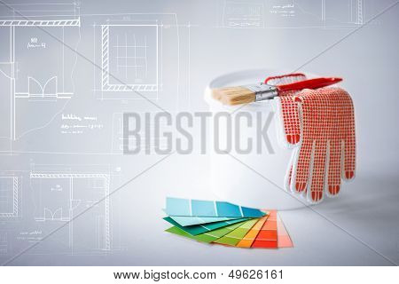 interior design and home renovation concept - paintbrush, paint pot, gloves, pantone samplers and blueprint