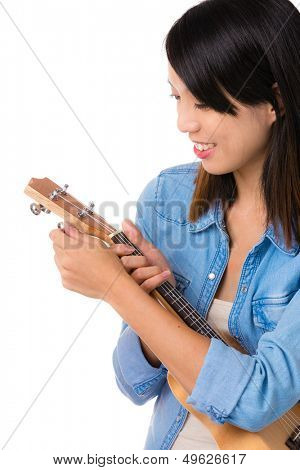Asian woman tuning ukelele